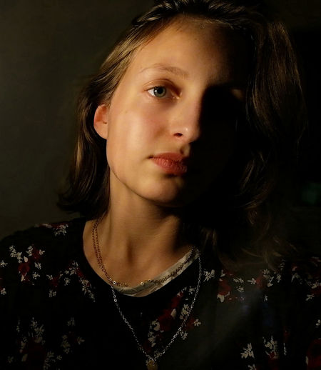 Close-up portrait of beautiful young woman against black background