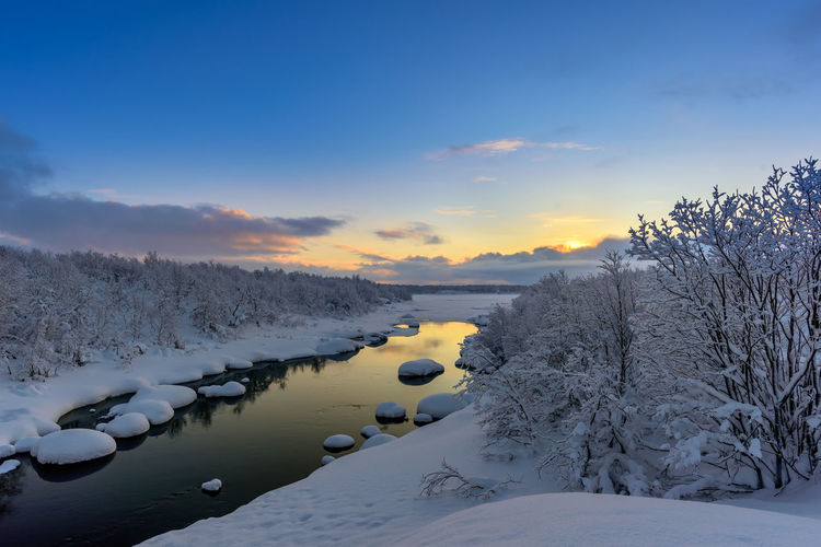 Winter Sunset on the Teriberka River in Russia's Kola Peninsula River Water Sunset Nature Sky Tree Winter Snow Frozen Tranquility Land Environment Beauty In Nature No People Copy Space Travel Destinations Tranquil Scene Non-urban Scene Cloud - Sky Cold Temperature Unspoiled Nature Scenics - Nature Pristine Nature