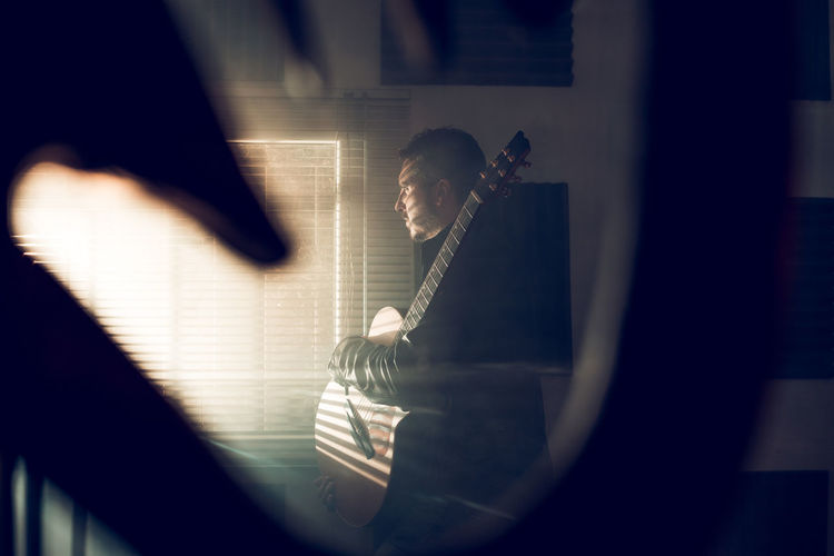 Man playing piano seen through window