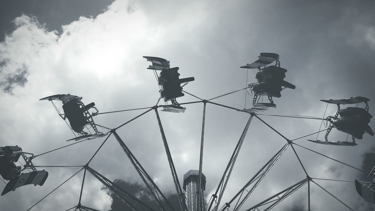 Low Angle View Of Carousel Against Cloudy Sky