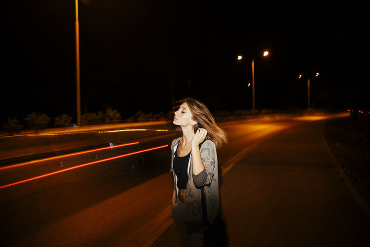 Blurred motion of woman standing on road at night