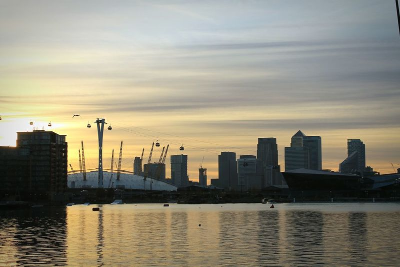 Thames river in front of city against sky during sunset