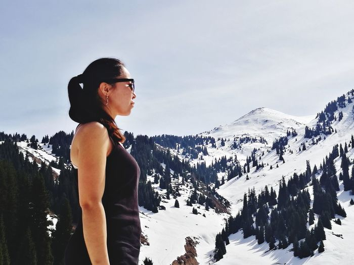 Side View Of Young Woman Looking At Snow Covered Mountains
