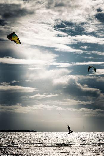 Silhouette man kiteboarding in sea against sky