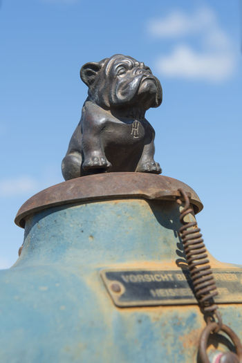 Bladel, Netherland - April 5, 2015; Lanz bulldog ornament on a old tractor, symbolising a famous german tractor brand Lanz Bulldog Ornament Tractor Brand Sculpture Blue Sky Argriculture Statue Low Angle View