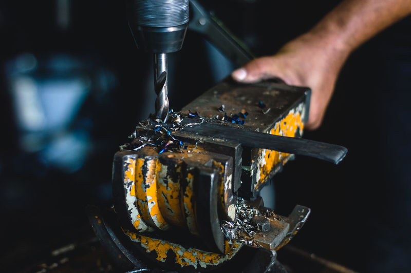 Close-up of person working on metal machine