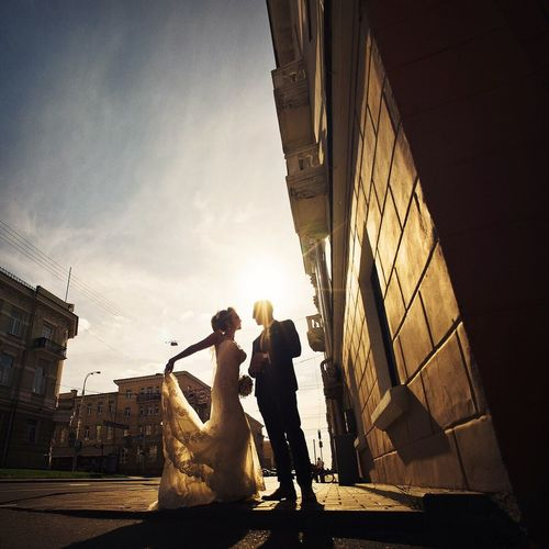 Bride And Groom On Street Against Cloudy Sky On Sunny Day