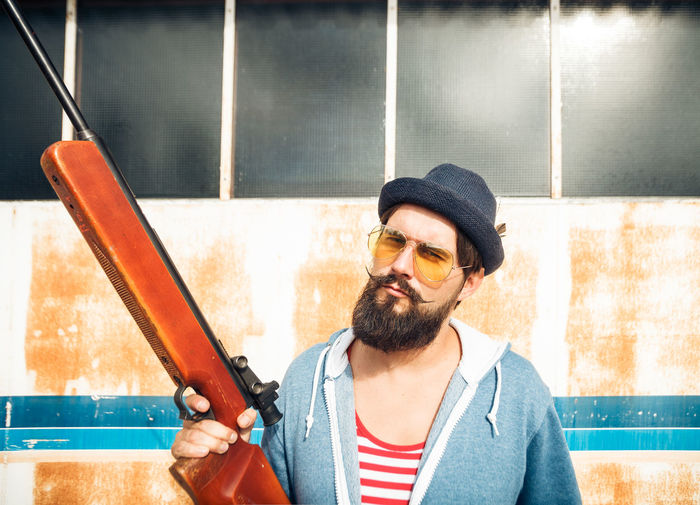 Fashion Gun Hunter Man Shoot Stripes Target Airgun Beard Clothing Facial Hair Front View Glasses Hat Hipster Jumpsuit Mid Adult One Person Onsie Pose Pyjama Riffle Rusty Sunglasses Weapon