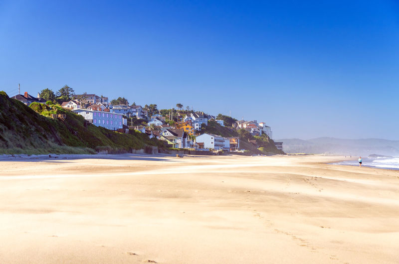 Scenic view of beach by town against clear blue sky