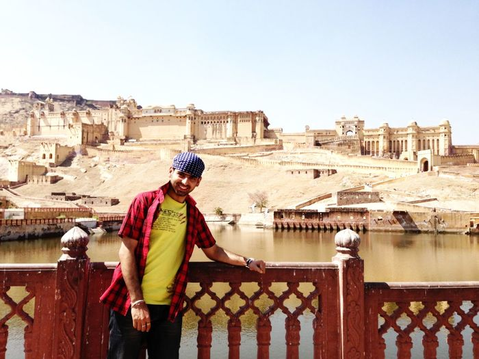 Young Man Standing At River By Amber Fort Against Sky