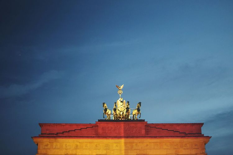 Low angle view of quadriga statue on brandenburg gate against sky