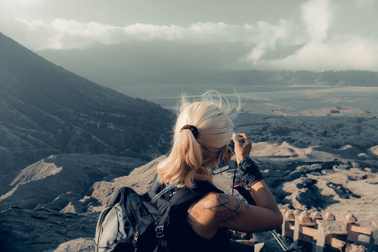 Side view of woman photographing on mountain against sky