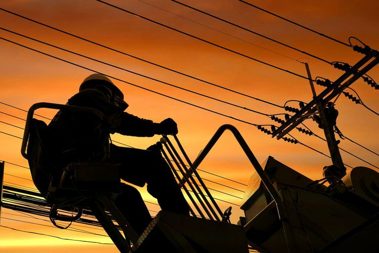 Low angle view of silhouette worker working over power line against orange sky during sunset