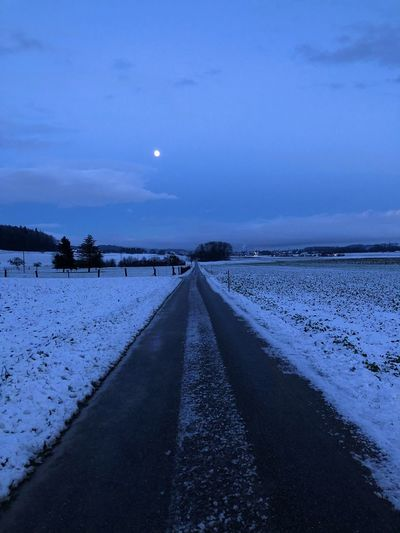 Road amidst snow against sky at dusk
