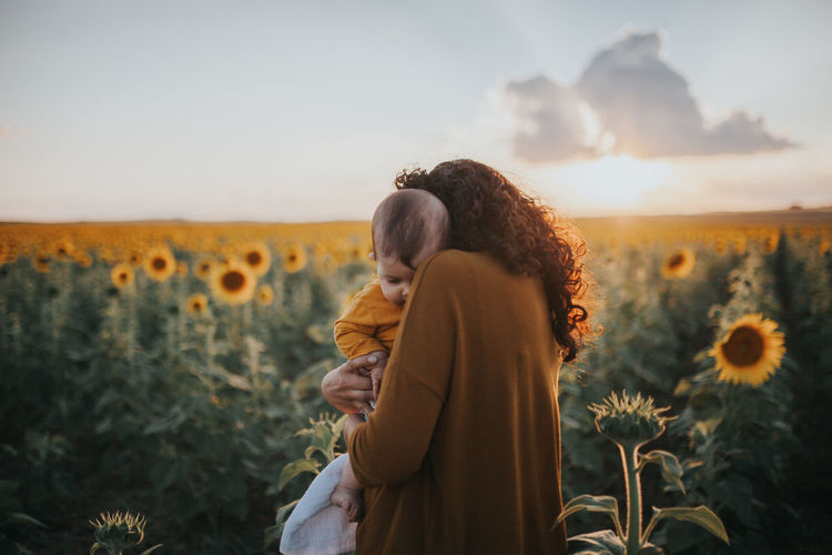 Mother Carrying Toddler Daughter In Sunflower Farm Against Sky