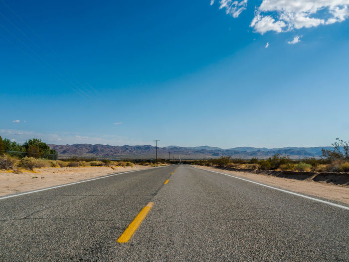 Low-level view of deserted road Desert Low Angle View Road Asphalt Beauty In Nature Blue Day Landscape Mountain Nature No People Outdoors Road Road Marking Scenics Sky The Way Forward Transportation