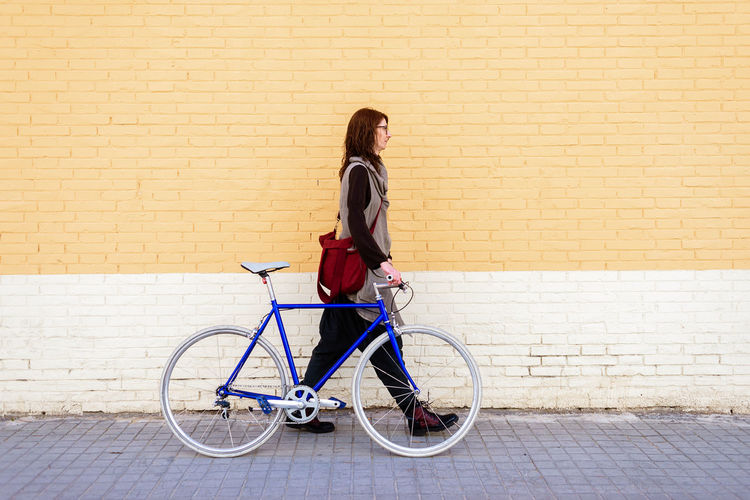 Full length of woman with bicycle standing against brick wall