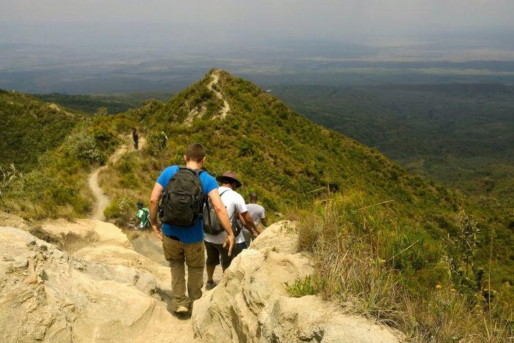 Rear view of men walking on mountain road