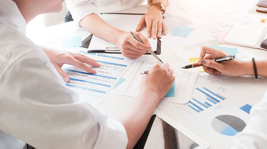 Business people Consulting and business planning. Adult Business Business Meeting Business Person Cooperation Coworker Hand Human Hand Indoors  Meeting Men Occupation Office Paper Pen People Planning Professional Occupation Real People Table Teamwork Working
