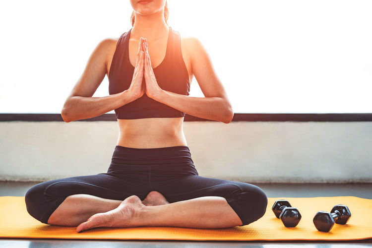 Low section of woman doing yoga at home