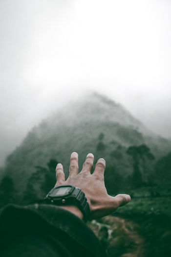 Cropped hand of man against mountain