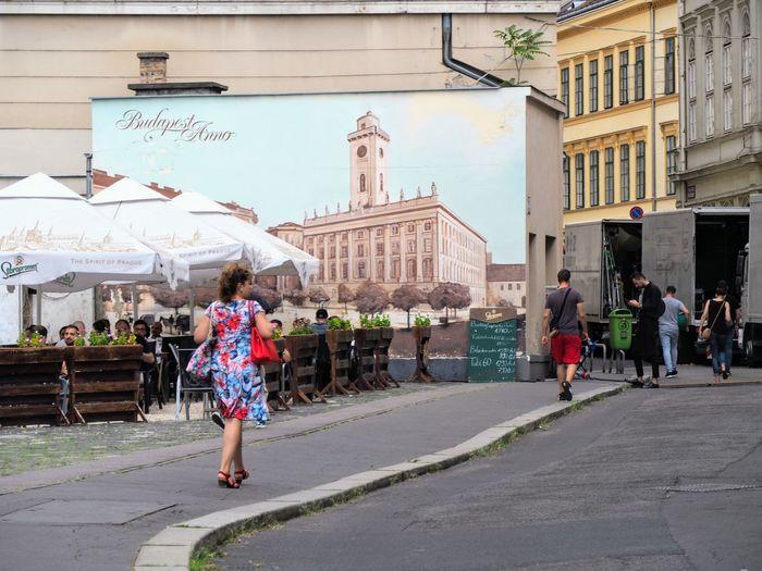 People walking on street against buildings in city