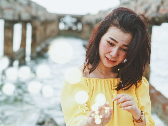 Woman holding light in hands. Adult Beautiful Woman Brown Hair Day Emotion Focus On Foreground Front View Hair Hairstyle Happiness Leisure Activity Lifestyles Long Hair Nature One Person Outdoors Portrait Real People Smiling Warm Clothing Women Young Adult Young Women