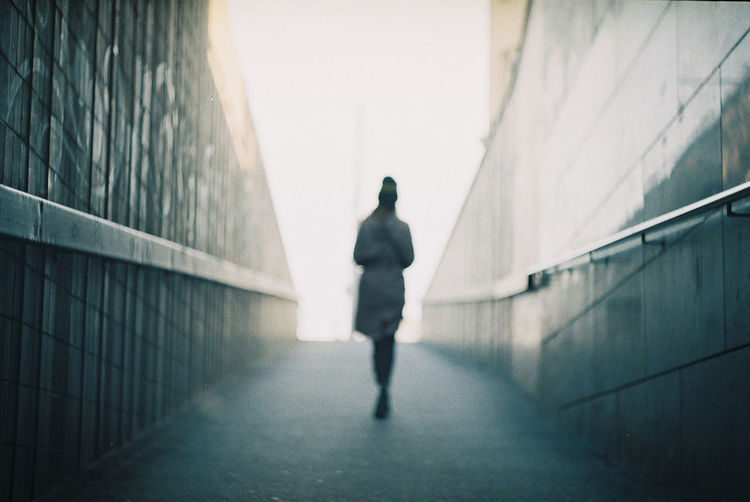 Rear View Of Woman Walking On Underground Walkway