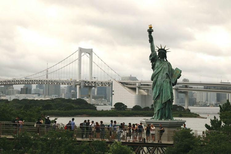 Statue of suspension bridge in city against cloudy sky