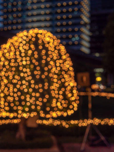 Emotion blurred of LED light decorate on tree around city. A beautiful of blurry background of bulb light in the park. Colorful of Christmas eve and happy new year cerebration, night city life.