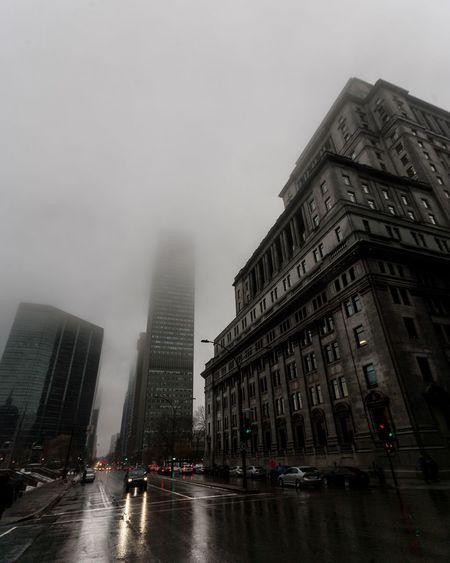 Buildings in city against sky during rainy season