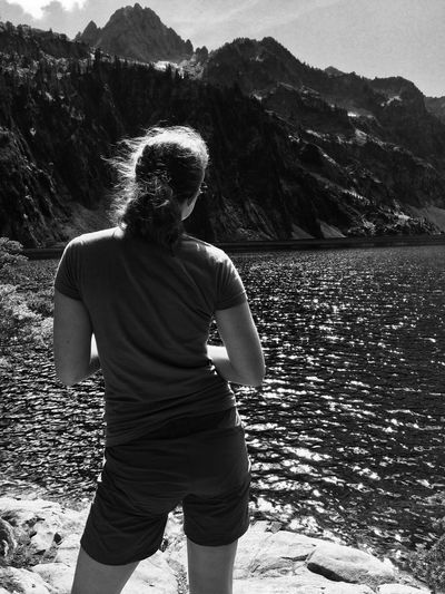 Rear view of woman standing by alpine lake and rocky mountains