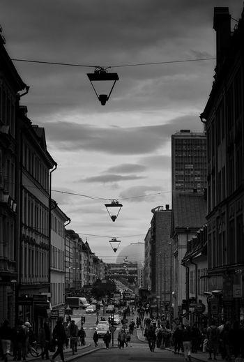 People on street amidst buildings against sky