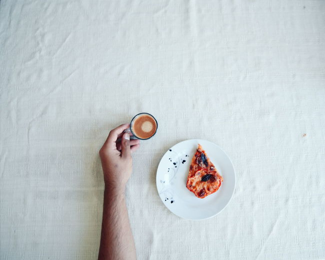 Cropped hand of man holding cup with coffee by pizza slice on table