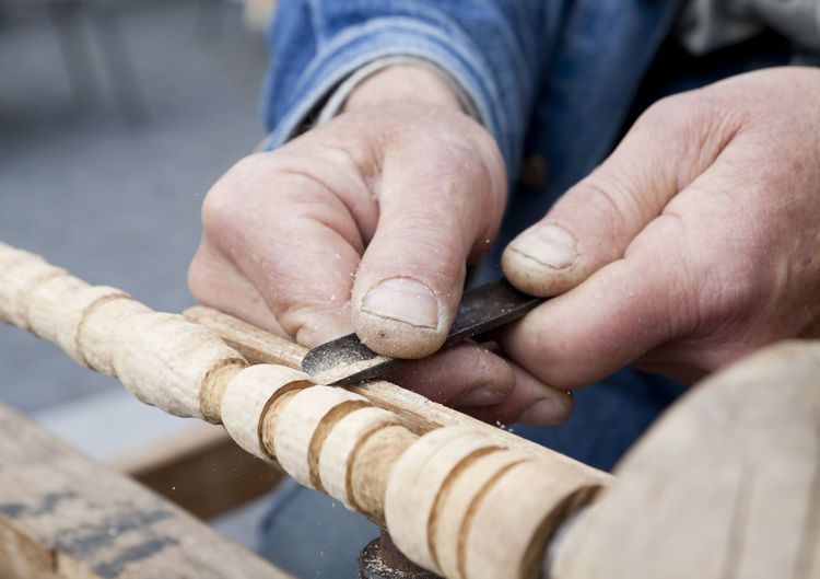 Cropped hands of carpenter carving wood at workshop