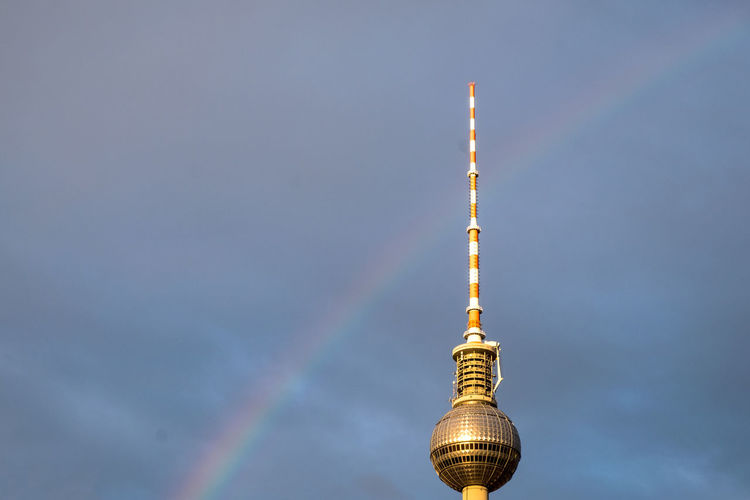 Low angle view of fernsehturm with rainbow against cloudy sky