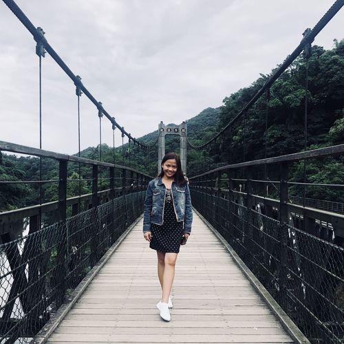Full length portrait of woman standing on footbridge against sky