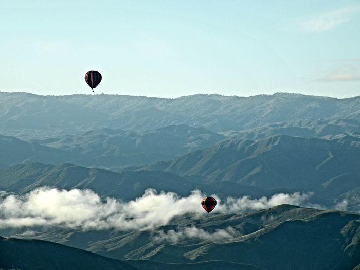 Kite flying over mountains against sky