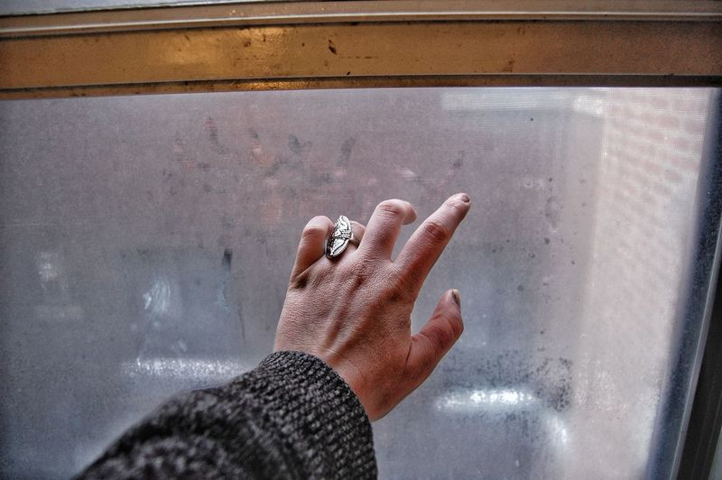 Cropped hand touching window