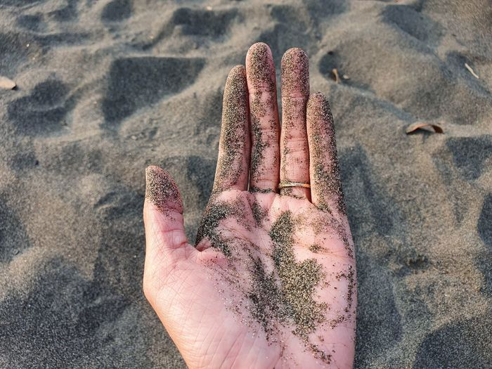 Cropped hand with sand at beach
