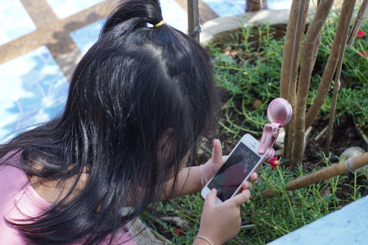 Four-year-old girl is intending to shoot with a mobile camera. Going Remote Thai Thai Girl Thailand Activity Black Hair Communication Connection Day Focus On Foreground Hair Hairstyle Headshot Holding Leisure Activity Lifestyles One Person Outdoors Photography Themes Plant Real People Technology Wireless Technology Women The Fashion Photographer - 2018 EyeEm Awards The Still Life Photographer - 2018 EyeEm Awards