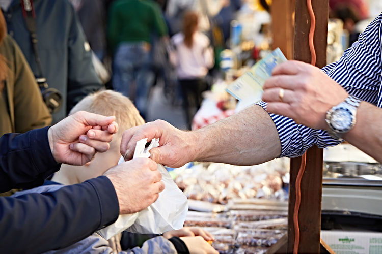 Cropped image of customer buying from vendor at market