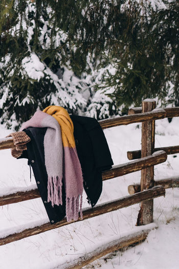 Coat and scarf hanging over a wooden fence