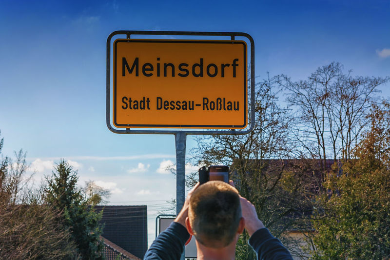 Town Entrance sign of the village Meinsdorf, town Dessau Rosslau in Germany. Text Tree Real People Western Script Sky Communication Nature One Person Plant Lifestyles Sign Leisure Activity Men Day Holding Technology Outdoors Personal Perspective Information Finger #NotYourCliche Love Letter