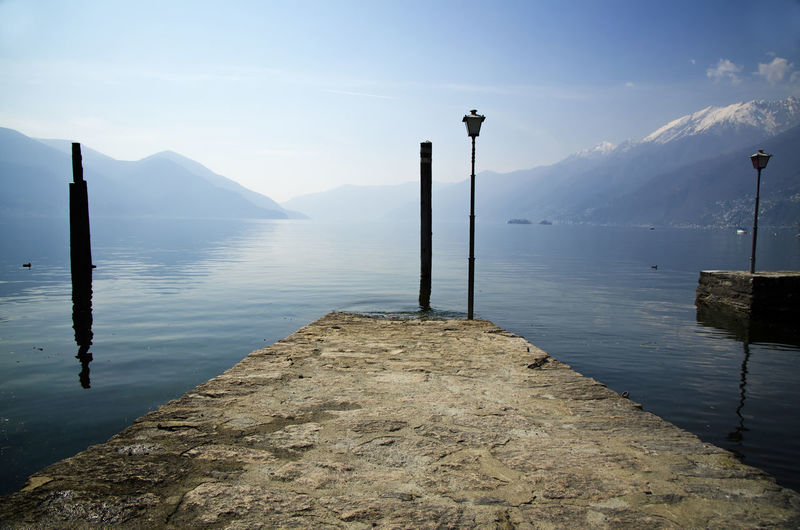 Pier with Street Lamp on Alpine Lake Maggiore with Mountain in Ascona, Switzerland. Pier Street Lamp Beauty In Nature Day Lake Lake Maggiore Mountain Mountain Range Nature No People Outdoors Scenics Sky Swiss Alps Tranquil Scene Tranquility Water