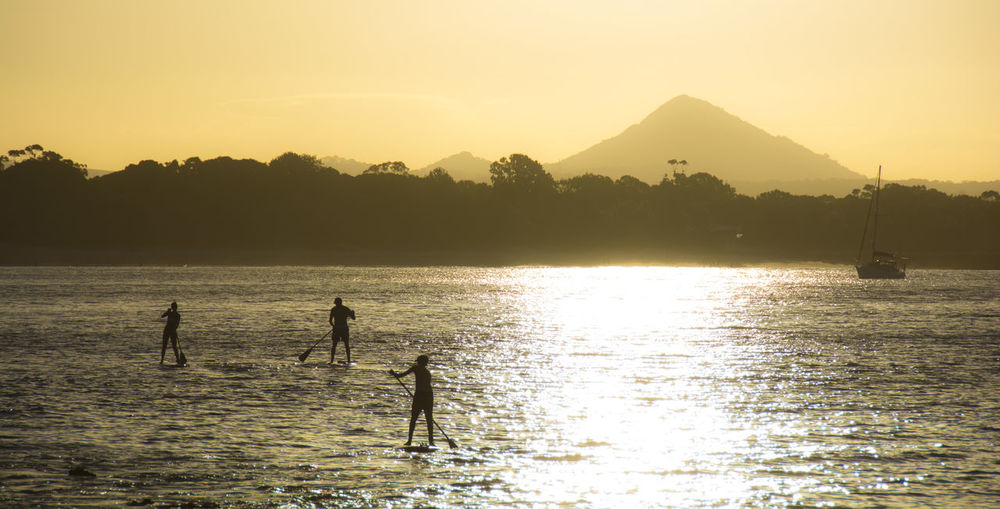 Silhouette people paddleboarding on sea against sky