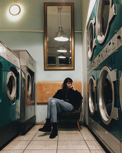 Woman Sitting On Chair Amidst Washing Machines At Laundromat