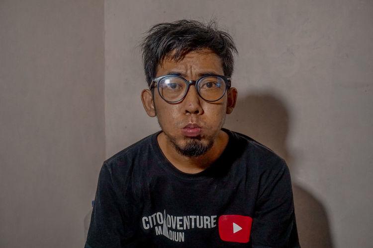 Portrait of man wearing eyeglasses standing against wall