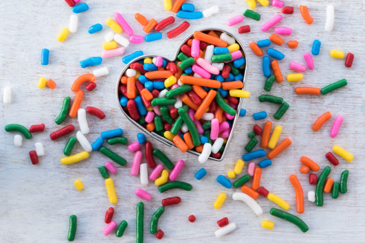 Close-up of colorful candies in heart shape container on table