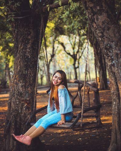 Full length portrait of woman sitting on swing in park